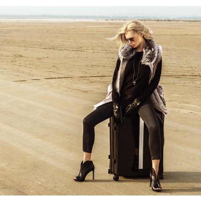Silver fox fur vest: Symetrie,; Jeans: Marani; sweater: Boss Orange; Belt: Maison  Anna Dorothea; pendant: Givenchy; Boots: Guess; leather gloves, Baldinini,; glasses, Oliver  Peoples,; suitcase: Benga.